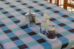 Colpo della cantina del pepe e del sale del primo piano sulla tavola quadrata di progettazione fotografie stock