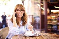 Colpo della donna invecchiata media che si siede nella caffetteria e che fa una chiamata fotografia stock