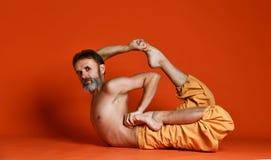 Colpo dello studio dell'uomo barbuto senior che fa le pose di yoga e che allunga le sue gambe senza camicia fotografia stock