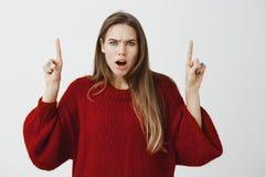Colpo dello studio di bella donna colpita dispiaciuta in maglione rosso alla moda, aggrottante le sopracciglia ed alzante i dito  Fotografie Stock Libere da Diritti