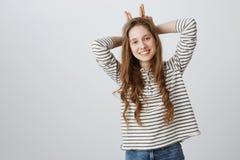 Colpo dello studio di tenersi per mano femminile adolescente caucasico felice positivo dietro la testa, imitando i corni, inclina Fotografia Stock