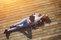 Colpo di angolo alto della giovane donna spensierata in vetri di estate che si trovano sul molo di legno al sole Immagini Stock