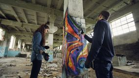 Colpo di angolo basso dei pittori dei graffiti che decorano fabbricato industriale abbandonato con le immagini luminose facendo u archivi video