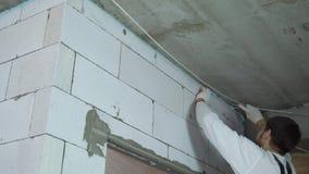Colpo di angolo basso del costruttore che rimuove eccessiva schiuma di montaggio dalla parete stock footage