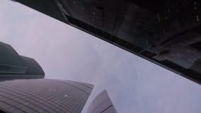 Colpo di angolo basso della macchina fotografica che gira davanti a moderno, costruzioni della torre dell'ufficio stock footage