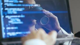 Colpo di doppia esposizione del programmatore del pirata informatico dell'uomo in occhiali che funzionano ad un computer portatil video d archivio