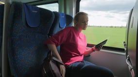 Colpo di giovane donna bionda che va lungo il treno e che cerca il suo posto del sedile, treno moderno della ferrovia, Vienna, Au stock footage