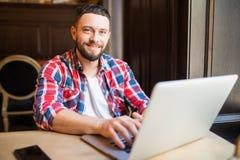 Colpo di giovane uomo d'affari che lavora al suo computer portatile in un negozio del caffè Fotografia Stock Libera da Diritti