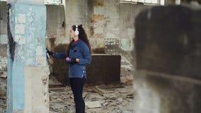 Colpo di inclinazione-su dei graffiti urbani moderni del disegno del pittore sull'alta colonna in magazzino abbandonato con la pi archivi video