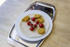 Colpo di prospettiva delle pepite di pollo e di piccoli pomodori freschi rossi sull'ampio piatto bianco come prima colazione con  immagine stock libera da diritti