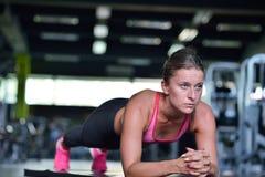 Colpo di una giovane donna di misura che fa allungando allenamento sul pavimento della palestra Fotografie Stock