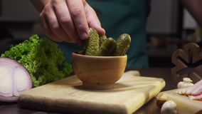 Colpo di zumata dello scorrevole: il cuoco unico prende il sottaceto dalla ciotola sul tavolo da cucina, verdure inscatolate, ing archivi video