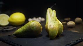 Colpo di zumata dello scorrevole: la pera succosa cruda è sul tavolo da cucina, la frutta fresca, gli ingredienti per macedonia,  stock footage