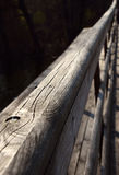 Colpo diagonale del corrimano del ponte di legno con il fondo scuro dell'acqua Immagini Stock Libere da Diritti