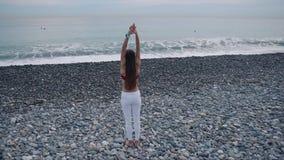 Colpo distante di una donna di yoga sulla spiaggia stock footage