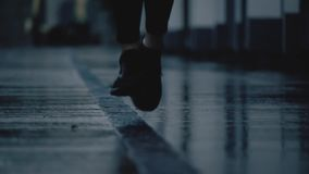 Colpo eccellente del primo piano del movimento lento dei piedi del corridore femminile che corrono sulla pavimentazione bagnata d video d archivio