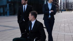 Colpo epico del maschio disabile che si siede sulla sedia a rotelle con i suoi colleghi video d archivio
