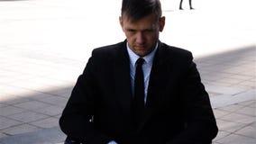 Colpo epico dell'uomo d'affari caucasico serio in una sedia a rotelle all'aperto video d archivio