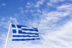 Colpo inferiore di prospettiva della bandiera d'ondeggiamento variopinta della Grecia con il fondo blu del cielo aperto a Smirne  fotografia stock libera da diritti