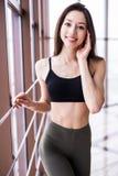 Colpo integrale della donna risoluta di forma fisica che cammina nella palestra del crossfit Sportiva muscolare che si scalda pri Immagine Stock