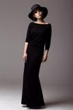 Colpo integrale di una donna in vestito e cappello neri lunghi Fotografie Stock Libere da Diritti