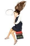 Colpo isolato della scolara premurosa che si siede sul mucchio dei libri Fotografie Stock
