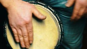 colpo 4k di un uomo che gioca su una fine del tamburo di bongo su Mano che spilla un bongo archivi video