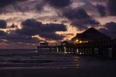 Colpo lunatico di una spiaggia dopo il tramonto, con il molo Fotografia Stock
