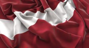 Colpo macro meravigliosamente d'ondeggiamento del primo piano increspato bandiera della Lettonia immagine stock