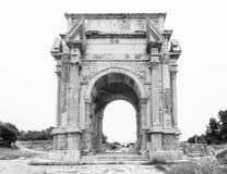 Colpo medio in bianco e nero dell'arco iconico di Settimio Severo alle rovine romane antiche di Leptis Magna in Libia fotografie stock libere da diritti