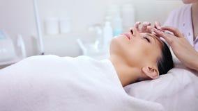 Colpo medio che si preoccupa estetista femminile che fa massaggio facciale al giovane cliente adorabile a mano stock footage