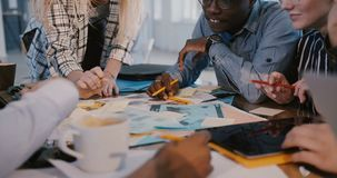 Colpo medio del gruppo commercializzante creativo multietnico che lavora al 'brainstorming' dietro la tavola, sorridere nero degl video d archivio