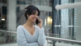 Colpo medio di conversazione di risata femminile asiatica sul telefono mentre camminando