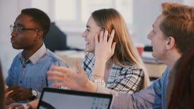 Colpo medio di giovane gruppo multietnico felice dei soci commerciali che parla, sorridente sul 'brainstorming' dietro la tavola  stock footage
