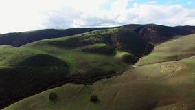 Colpo meraviglioso di ampi campi verdi variopinti e delle colline da sopra stock footage