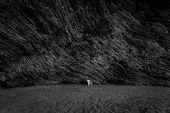 Colpo monocromatico della spiaggia abbandonata con l'alta scogliera Immagini Stock