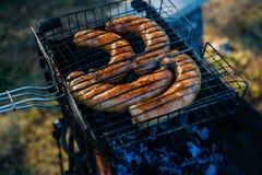 Colpo naturale di grigliare le salsiccie sulla griglia del barbecue BBQ nel giardino fotografia stock
