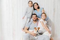 Colpo orizzontale della posa amichevole della famiglia insieme contro la b bianca immagini stock