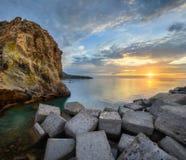 Colpo panoramico dei blocchetti del cubo del frangiflutti alla costa dell'isola ad alba, isole Eolian, Sicilia, Italia di Vulcano immagine stock