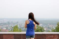 Colpo posteriore di una ragazza che esamina l'orizzonte Immagine Stock