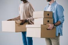 colpo potato degli uomini multietnici che tengono le scatole di cartone immagine stock