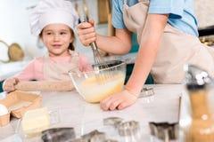 colpo potato dei bambini in grembiuli che preparano insieme pasta immagine stock