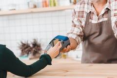 colpo potato del barista che dà il terminale di posizione al cliente per pagare fotografia stock libera da diritti
