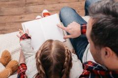 colpo potato del libro di lettura della figlia e del padre e di indicare con il dito fotografie stock libere da diritti