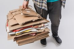 colpo potato del mucchio della tenuta dell'uomo delle scatole di cartone piegate isolate su grigio, riciclando concetto Fotografia Stock
