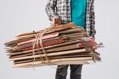 colpo potato del mucchio della tenuta dell'uomo delle scatole di cartone piegate isolate su grigio, riciclando concetto Fotografia Stock Libera da Diritti