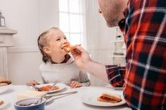 colpo potato del padre che alimenta piccola figlia adorabile con pane tostato immagine stock libera da diritti
