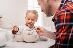 colpo potato del padre e di piccola figlia che mangiano i fiocchi di mais immagini stock libere da diritti