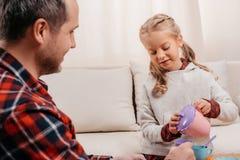 colpo potato del padre e di piccola figlia sveglia che hanno ricevimento pomeridiano fotografia stock libera da diritti