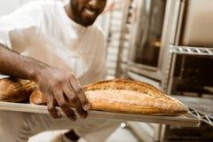 colpo potato del panettiere afroamericano con il vassoio di pagnotte fresche fotografia stock libera da diritti